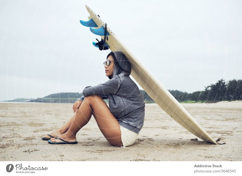 Relaxed woman sitting on beach with surfboard on head surfer rest casual sand relax sporty tranquil sunglasses lifestyle nature seashore seaside weekend ocean