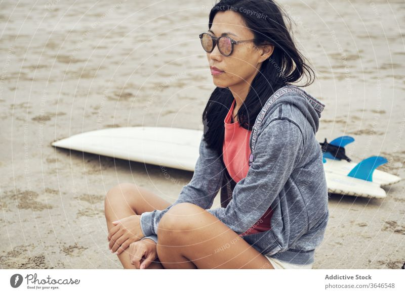 Calm Asian woman sitting on beach near surfboard surfer sandy rest thoughtful casual sunglasses seaside relax young sporty tranquil lifestyle nature seashore