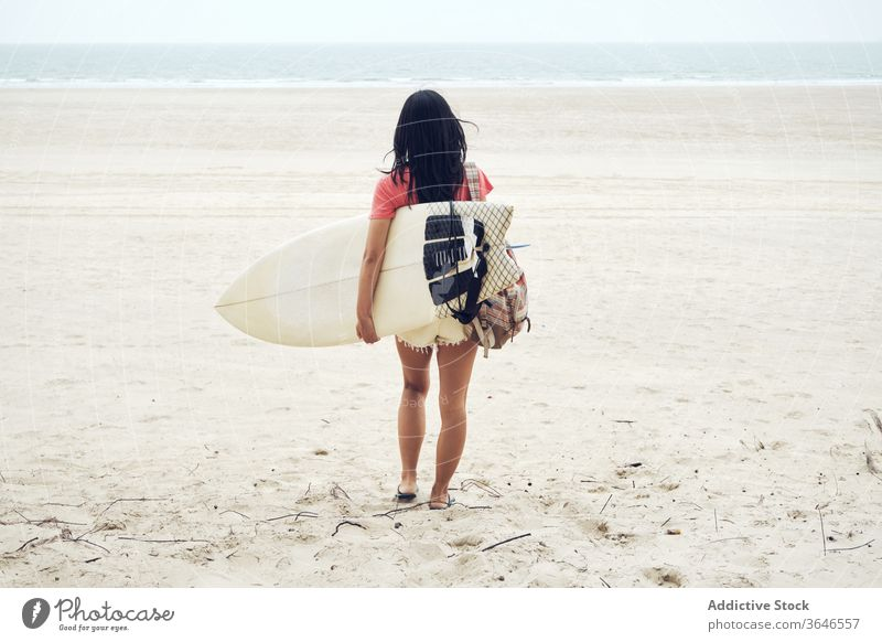 Anonymous female surfer walking on beach with surfboard woman sandy carry content sea casual seaside carefree activity young sporty tranquil lifestyle