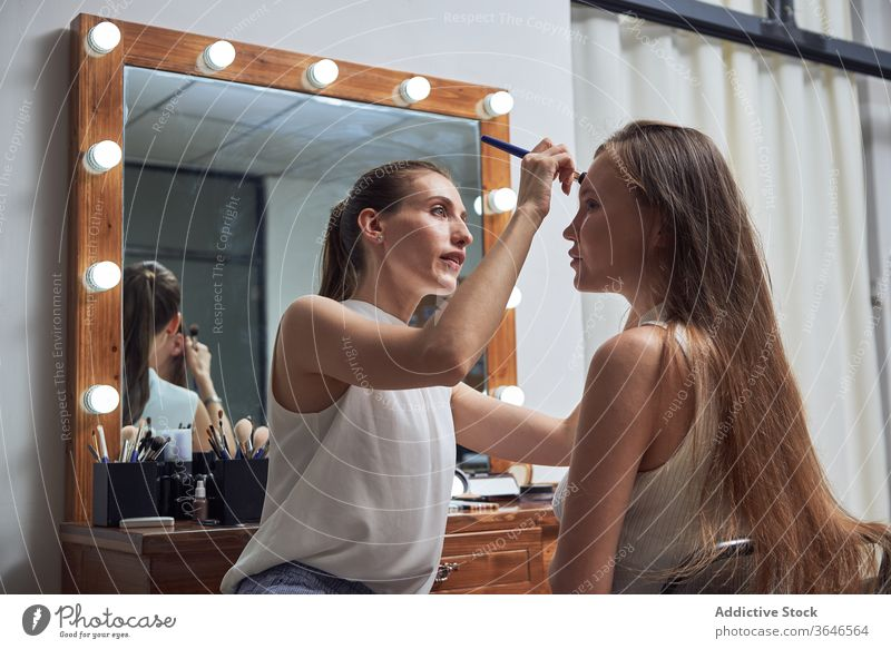 Professional visagiste applying makeup on model face brush salon mirror light positive concentrate cosmetic client care work serious skill creative process