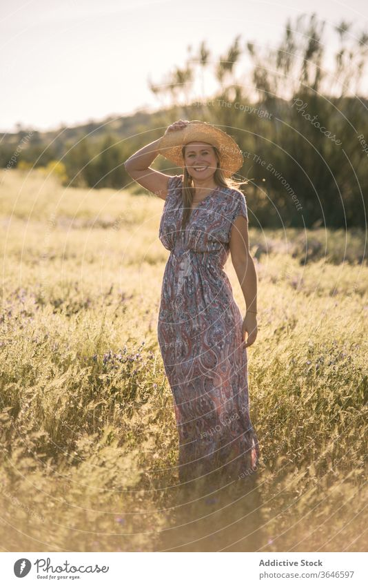 Charming woman in green field summer enjoy dress meadow sunny straw hat smile nature female cheerful vacation trendy stand freedom weekend daytime carefree rest