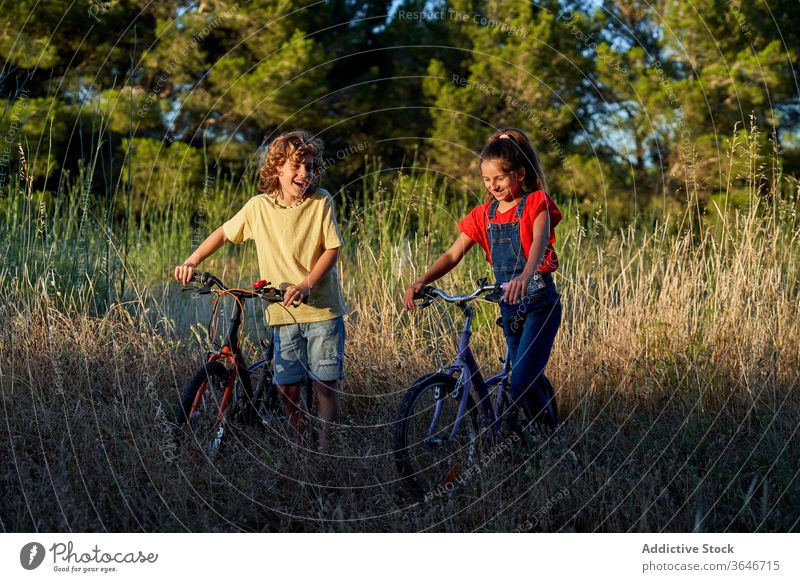 Ten-year-old boy and girl cycling through the countryside joy smiling kid bicycle enjoyment lifestyle children fun outdoorsy bike exploration exercising