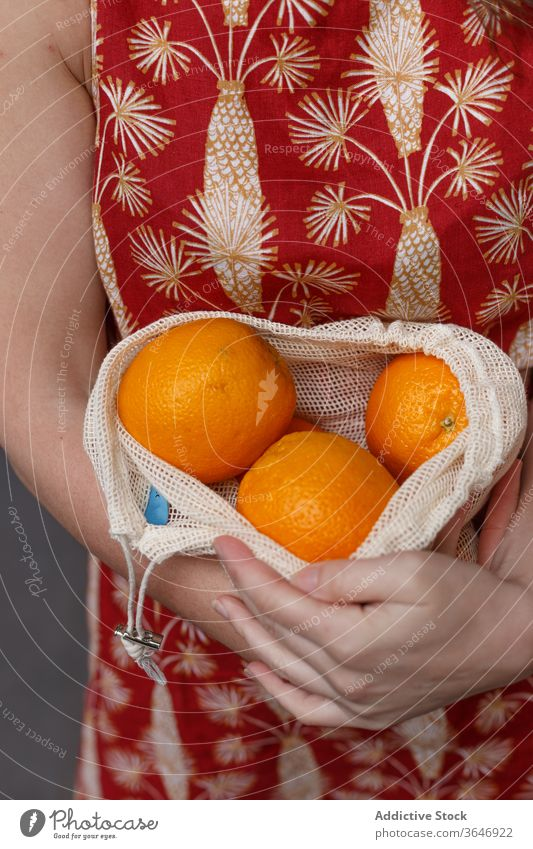 Crop woman with fresh fruits in string bag ripe orange shopping bag reuse eco friendly healthy food female ecology summer purchase grocery stand shopper