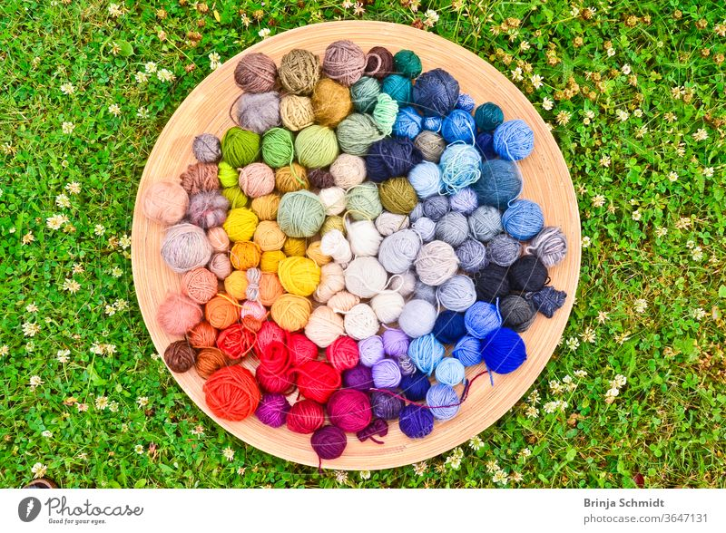 Many colorful balls of wool in a flat wooden bowl lying on the ground in the grass texture leisure pattern needlework creative textile knit work woven cotton
