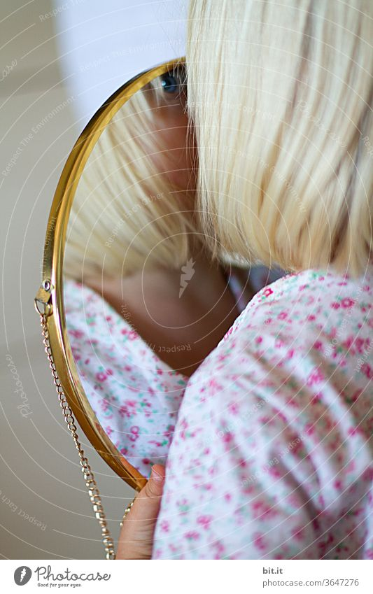At home, in a bright apartment, blonde girl holds a golden mirror in her hand and looks at it, curiously identifying her reflection. Childlike, playful self-observation, perception. Blue eye of a child in a mirror with a golden frame. Two.