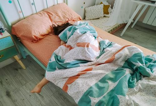 Girl sleeping covered up in her bed unrecognizable lazy girl sleepy morning deeply asleep bedroom young pillow tired female home caucasian indoor