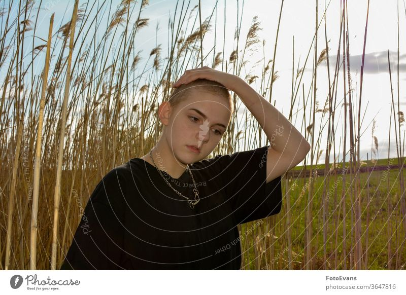 Girl  with very short hair  in nature, hand on the top of the head grass portrait sick fashion young cancer jewelry female attractive girl hair loss