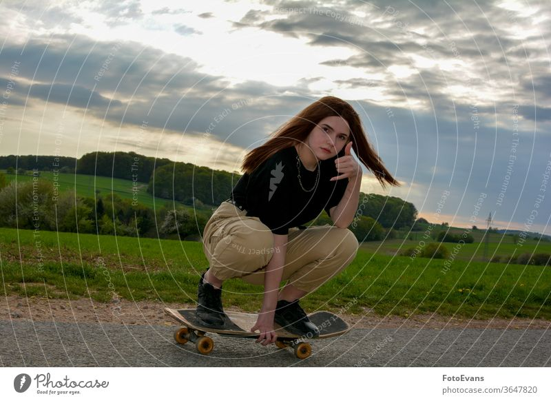 Young girl skates on a road in nature workout sporty enjoying fashion day beauty skating hand female attractive real fit hobby real person asphalt hair