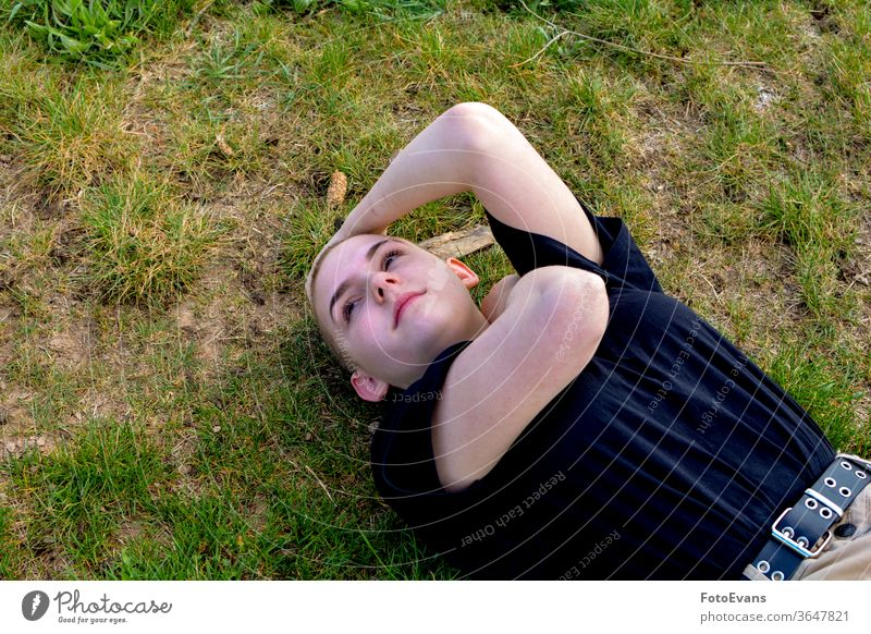 Girl with very short hair lies in the grass, arms on the neck and head portrait sick nature medicine fashion young beauty cancer ground female attractive girl