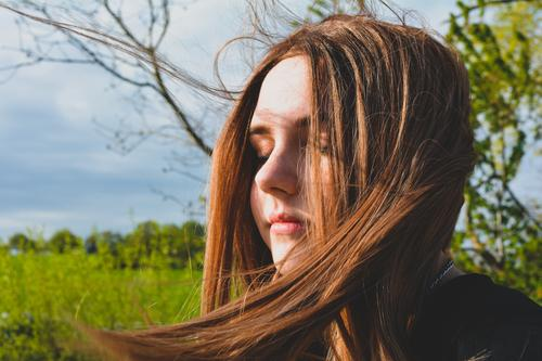 Girl stands with eyes closed in sunlight portrait enjoying nature fashion day beauty modern attractive girl tree style hair teenager person closed eyes branches