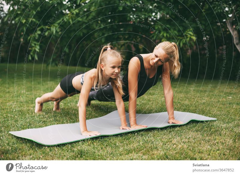 Mom and daughter play sports on the green grass near their home. Outdoor sports and fitness. Healthy sport lifestyle yoga outdoors mother home workout woman
