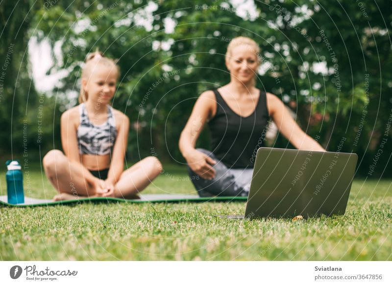 Mother and daughter practice online outdoors near their home during quarantine self-isolation during a pandemic. The family goes in for sports online from home together. Healthy lifestyle