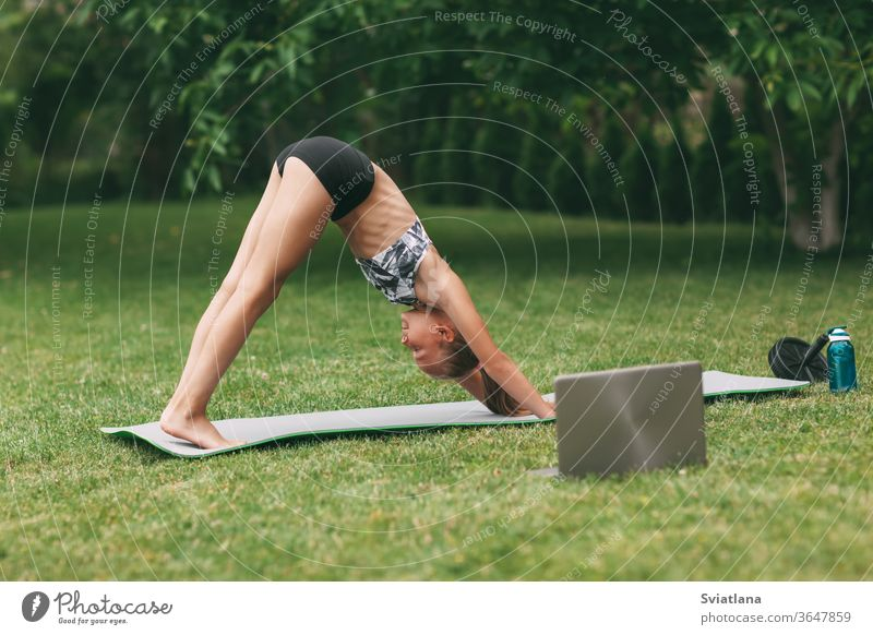 A teenage girl practices an online outdoor lesson near her home during quarantine self-isolation during a pandemic. Playing sports. Healthy lifestyle yoga