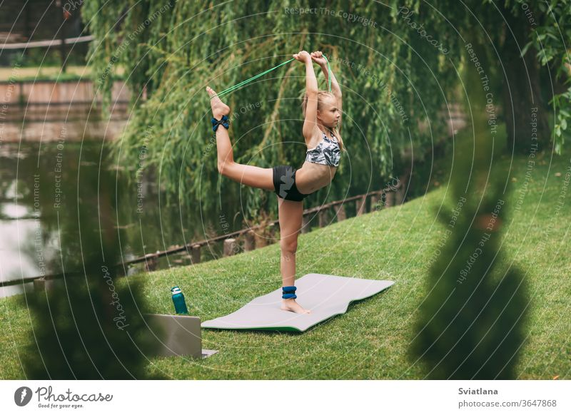 A teenage girl plays sports games near her home during quarantine self-isolation. Playing sports. Healthy lifestyle yoga outdoors mother daughter home workout