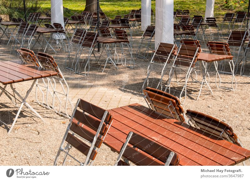 empty chairs and tables folded up in a beer garden Corona crisis rules of conduct ban on going out social distance restaurant parasols wooden chair