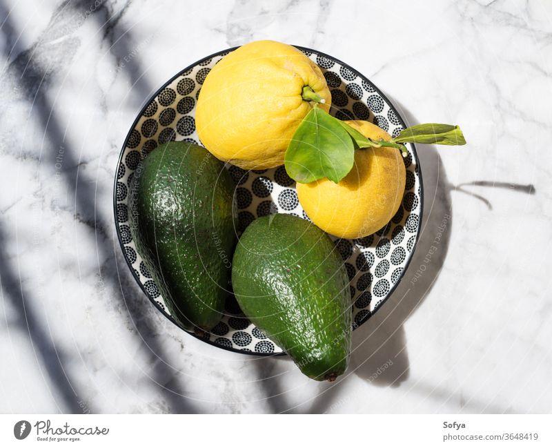 Avocado and lemons in a ceramic dish avocado marble flat lay fat food keto table natural hard light outdoors top view citrus vegetable fruit fresh summer