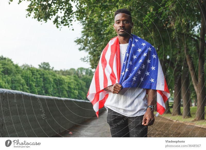 Handsome Afro American man with USA flag on his shoulders seriously looking at camera, standing outdoors. Day summer american male black african expat