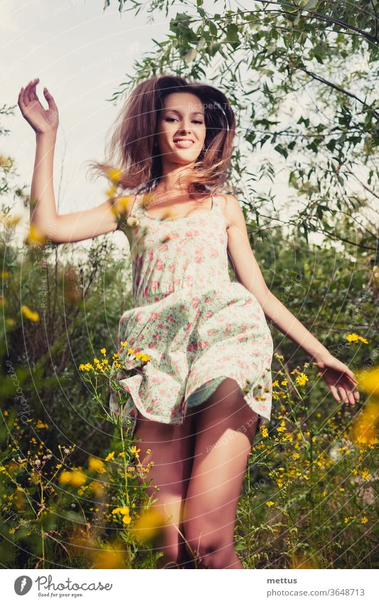 Happy girl. Blond haired woman dancing in the tall grass in the summertime ecstatically happy legs dance part of body dress jump active female young beauty