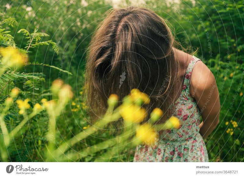 Beautiful blonde in a summer field is standing hiding her face by her hair for hiding emotions. dress candid shot beautiful fashion spring people young girl