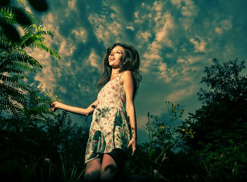 Jolly girl is dancing in tall grass in front of the dramatic sky. High jump in spring fields. She is dressed in light summer dress. blonde running freedom wind