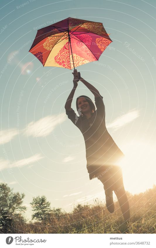 A young body-positive girl dances with a colored umbrella in a meadow illuminated by the sun at sunset. female freedom happy dress emotion classic person image