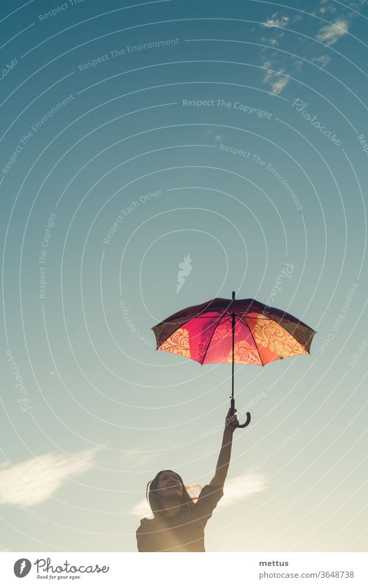Jolly girl holding colorful umbrella in her hands in front of the sky with space clouds, a lot of copyspace female freedom happy dress emotion classic person