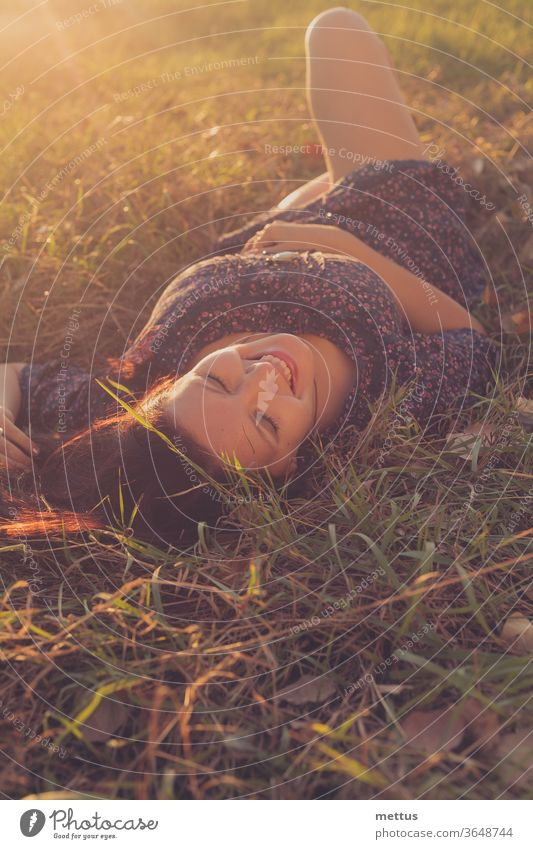 Happy girl is lying down in autumnal grass and laughing backlit by sunset sky activity back view bare legs communication crossed legs crosslegged female green