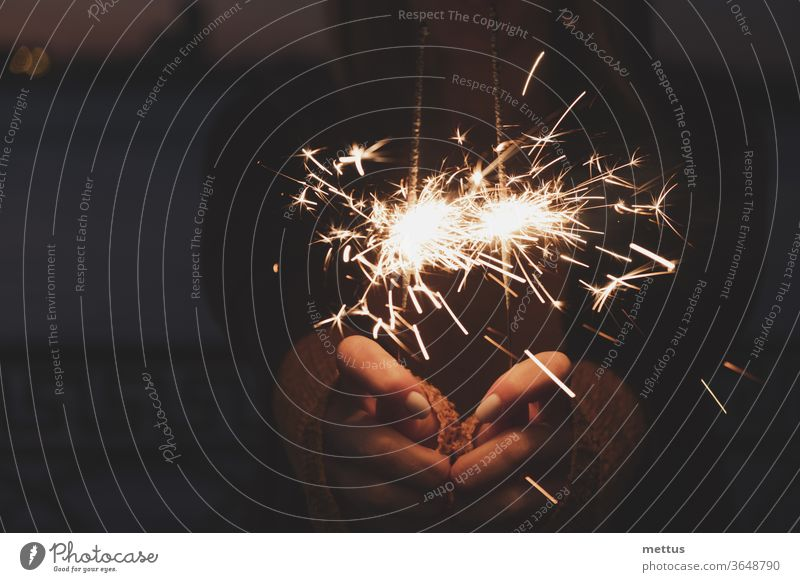 Female hands holding two burning sparklers award bokeh celebrating congratulations eve exploding explosion flame flare glow laughing magic occasion star bengal