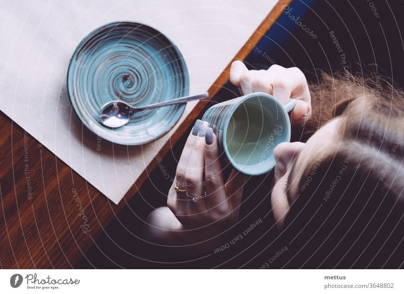 A view from above of a girl drinking tea from a small cup. above view hot drink nostalgia person female sitting top of head loneliness portrait express indoor