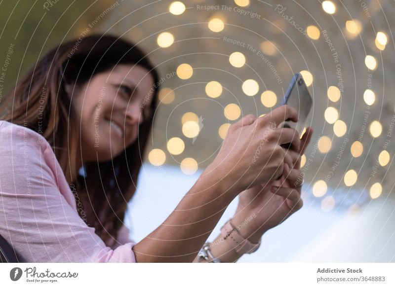 Smiling woman using smartphone outside take photo content illuminate garland memory moment female camera mobile gadget photography cellphone device smile