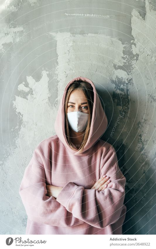 Woman in sterile mask standing near wall during quarantine period woman self isolation discontent coronavirus at home concrete domestic social distancing casual