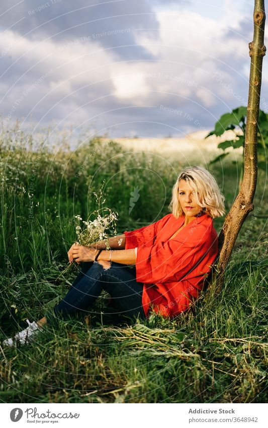 Relaxed woman resting on grassy field countryside trunk nature peaceful rural harmony idyllic daytime relax ground tranquil serene tree quiet flora casual