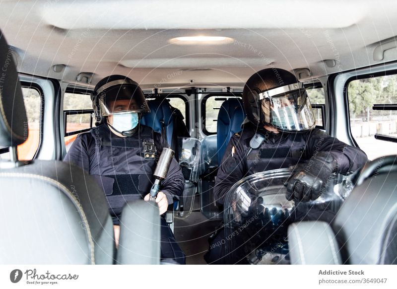 Police officer equipped with protective uniform in van with rifle man police operation street professional assault force service safety male helmet body armor