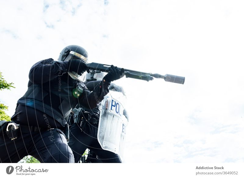 Professional policemen in protective gear during dangerous operation swat fight assault rifle shield equipment uniform partner helmet security weapon service