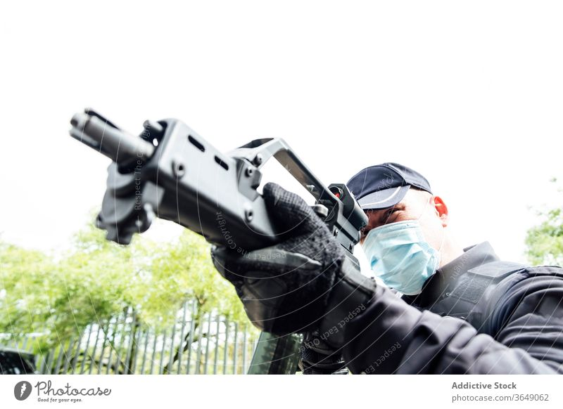 Concentrated policeman with submachine gun during assault aim operation protect serious swat safety danger professional equipment male uniform mask security