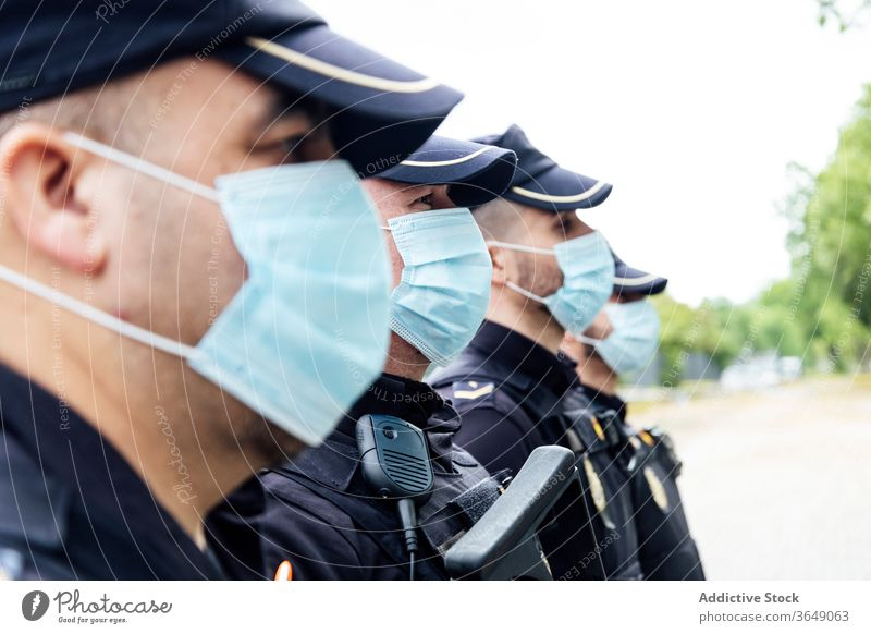 Policemen in medical masks standing on street against service vans patrol police protect control serious safety work professional secure squad uniform gun