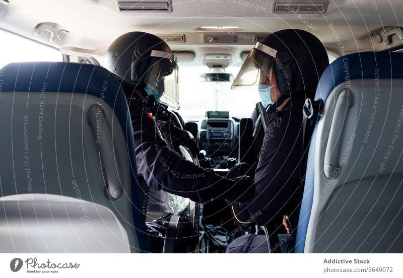 Police officers in squad car during service men set police equipment gear safety protect professional uniform partner medical mask speak vehicle transport job