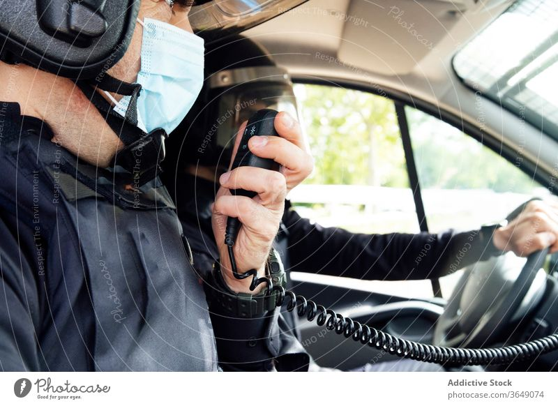 Anonymous police officers in squad car during service men talk radio set equipment gear safety protect professional uniform partner medical mask speak vehicle