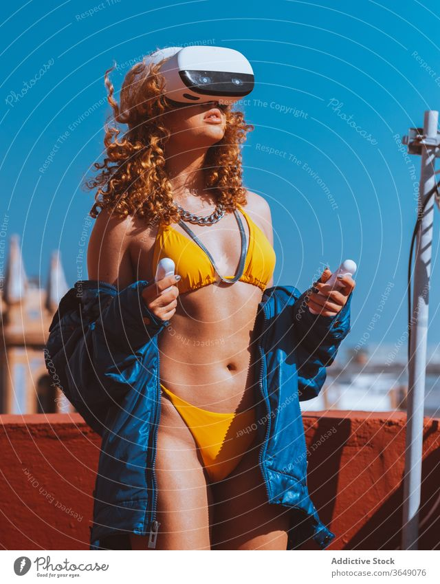 Female tourist in VR headset and swimsuit watching video outdoors vr entertain experience sunbath terrace fun immerse using wireless device beauty enjoy goggles