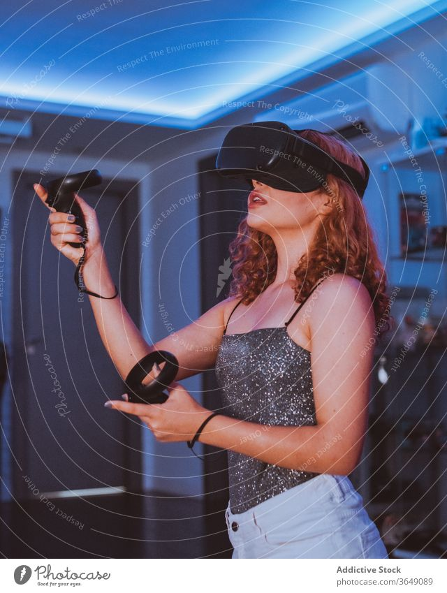 Anonymous woman playing game in VR goggles at home vr headset experience entertain controller video game immerse mouth opened neon using technology flat