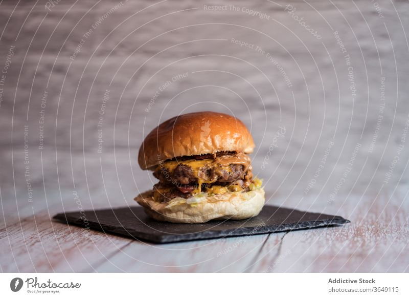 Delicious burger on slate board in cafe appetizing delicious serve hamburger cutlet tasty fast food cuisine wooden table sauce lunch junk food meal fresh meat