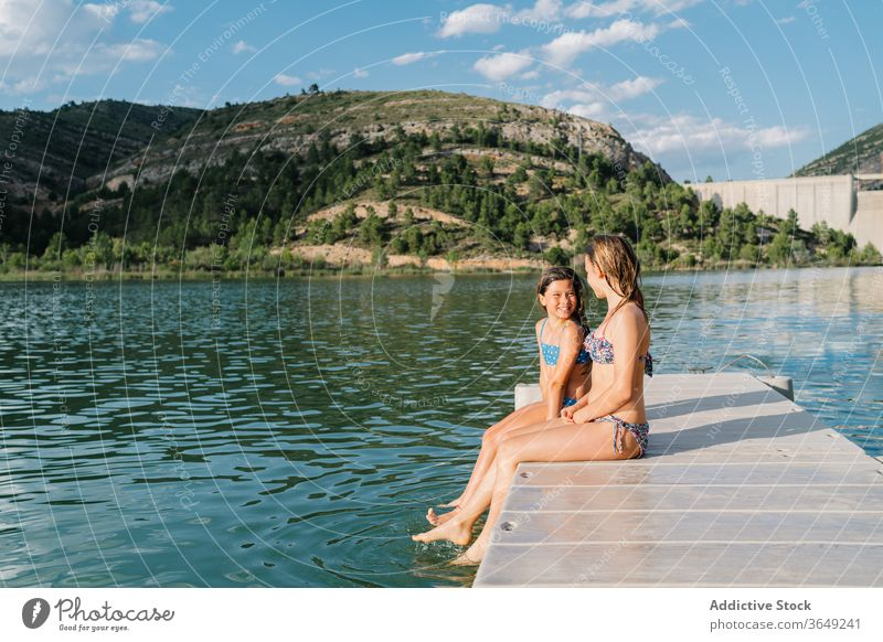 Carefree sisters resting on pier in summer vacation swimwear bikini girl lake quay cheerful together childhood smile friendship relax sit joy weekend