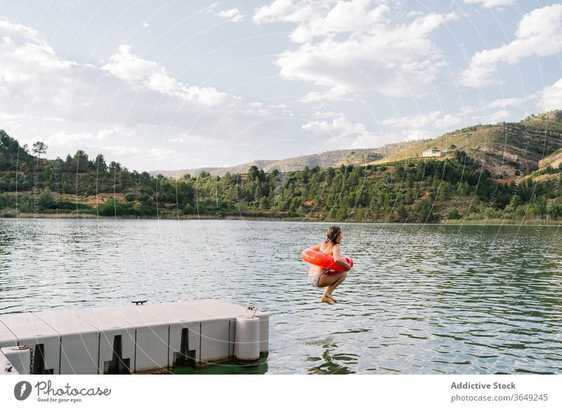 Girl jumping into lake with inflatable ring rubber girl pond bikini summer vacation having fun teenage moment water happy recreation relax holiday joy freedom