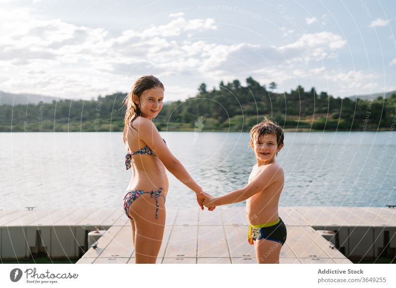 Siblings on wooden pier holding hands lake children summer vacation sibling together swimwear quay brother sister unity friendly friendship happy water smile