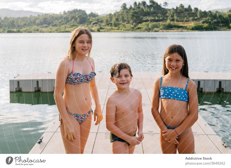 Group of cheerful siblings on wooden pier lake children summer vacation together group swimwear quay brother sister unity friendly friendship happy water rest