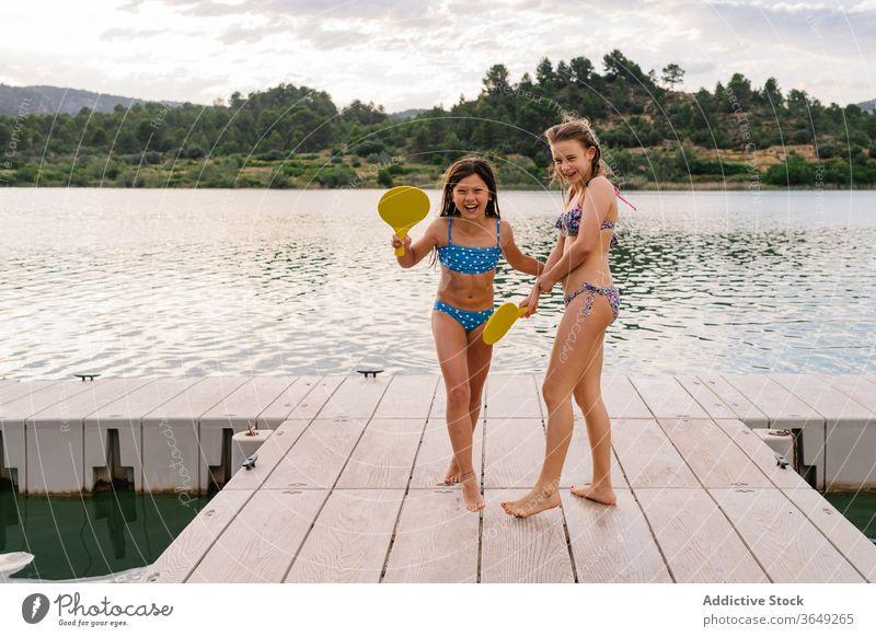 Happy girls playing beach tennis on pier lake sister active enjoy holiday having fun bikini summer ball racket teenage quay wooden vacation happy pond delight