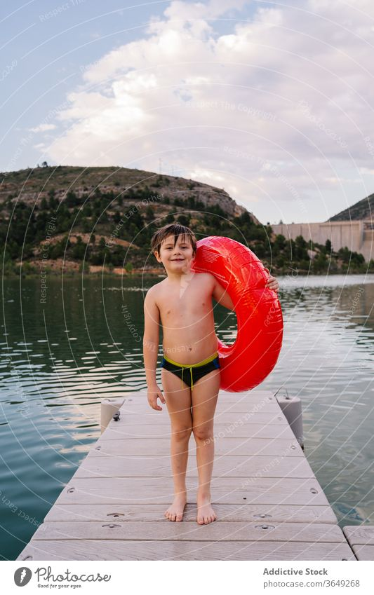 Boy with inflatable ring in lake boy rubber pond summer vacation cute smile having fun kid child water happy innocent cheerful childhood relax holiday joy