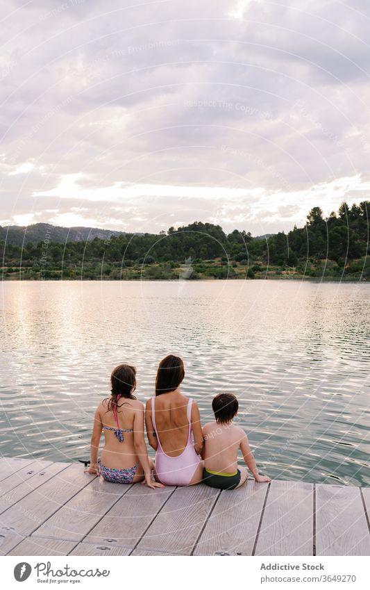 Calm children enjoying amazing view of lake vacation summer admire calm pond swimwear sibling scenery majestic together relationship friendship friendly bonding