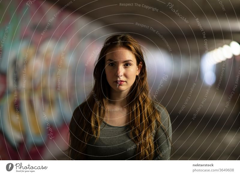 Portrait of a Young Woman Standing in Tunnel portrait female one person girl close up confident young woman underpass selective focus headshot