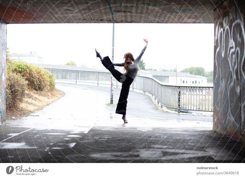 One Leg Hold Ballet in Front of City Underpass Entrance stand dancer female one leg hold one person girl tunnel underpass rainy elegance grace modern dance
